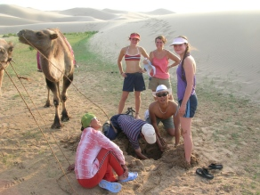 Crunching grainy bits between our teeth, we returned to the lower edges of the dunes where we'd left the camels and found a curious hole our two guides had dug. They explained they were letting the camels have a drink and showed us the little pool of mucky water sitting in the bottom.